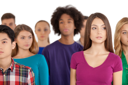 alone in crowd: Loneliness in a crowd. Frustrated young woman standing among multi-ethnic group of people and looking away Stock Photo