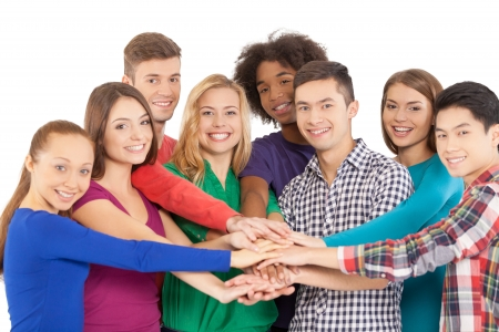 We are strong when we together. Cheerful group of multi-ethnic people holding hands together and smiling at camera while standing isolated on white Stock Photo