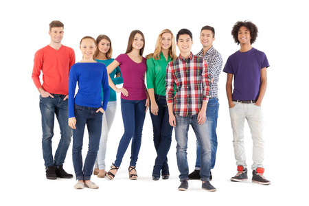 Casual people. Full length of cheerful young people smiling at camera while standing isolated on white