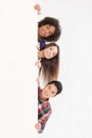 Hello! Cheerful young multi-ethnic people looking out of copy space and smiling at camera while isolated on white
