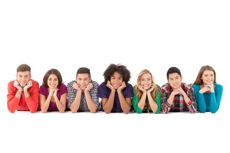 Gente ocasional. Jóvenes multiétnicas alegres acostado de frente y sonriendo mientras aislados en blanco