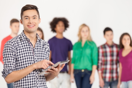 Join a digital age. Cheerful young man holding digital tablet while his friends standing on background photo