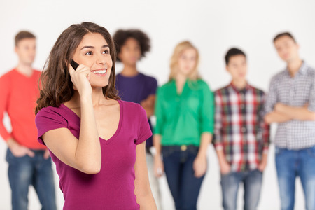 Always in touch. Cheerful young woman talking on the mobile phone while his friends standing on background photo