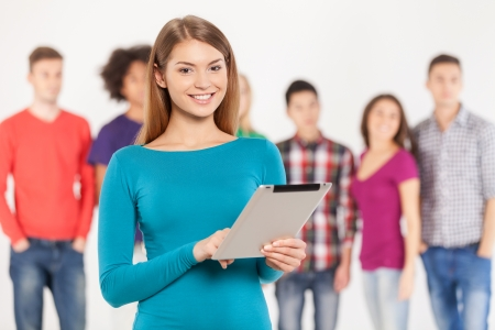 Join a digital age. Cheerful young woman holding digital tablet while his friends standing on background photo