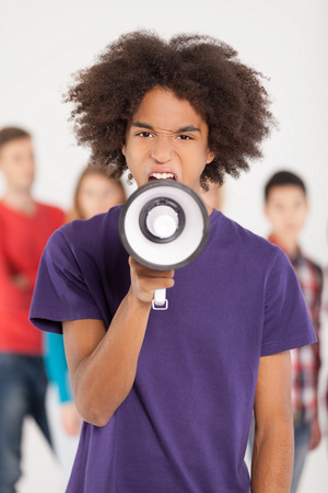 Hey you! Young African teenager shouting at megaphone while his friends standing on background photo
