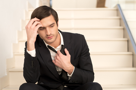 distraught: Sick and tired. Depressed young man in formalwear holding head in hand and taking off his necktie while sitting on staircase