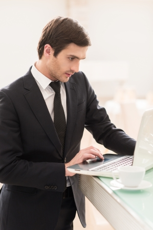 coffeebreak: He is always connected. Confident young man in formalwear using his laptop while standing at the bar