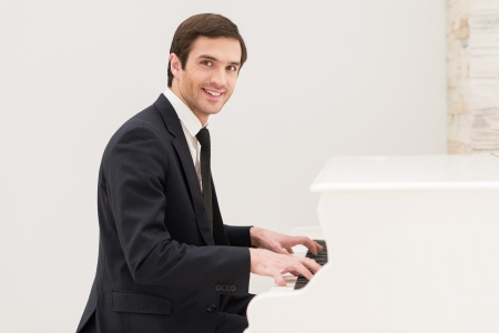 Piano man. Cheerful young man in formalwear playing piano and looking at camera Stock Photo