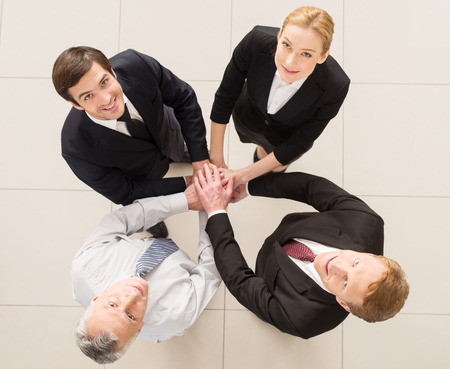 clasping: Yes, we are the best! Top view of four cheerful people in formalwear clasping their hands together and looking at camera