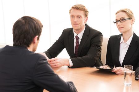 entrevista de trabajo: Entrevista de trabajo. Vista trasera de un joven en ropa formal sentado frente a dos otros hombres de negocios