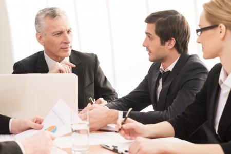 business man laptop: Hombres de negocios en la reuni�n. Cuatro hombres de negocios en ropa formal comunicarse mientras est� sentado juntos en la reuni�n