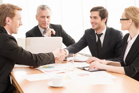 four hands: Welcome on board! Four business people sitting at the table while two of them shaking hands and smiling