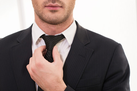 adjusting: Good looking business. Cropped image of young man in formalwear adjusting his necktie