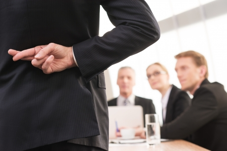 Liegen? Achteraanzicht van de mens in formalwear houden de vingers gekruist achter zijn rug terwijl drie mensen zitten op de achtergrond