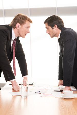 conflicting: Business people conflicting. Two young men in formalwear conflicting while standing face to face
