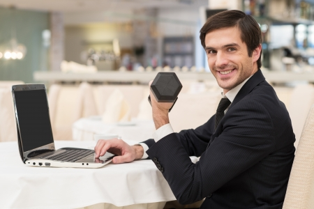 Sports and business. Cheerful young man in formalwear sitting at laptop and holding a dumbbell photo