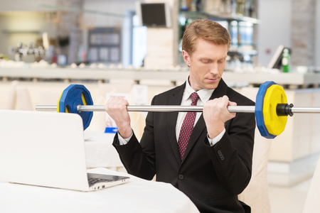 I choose healthy lifestyle. Confident young red hair man in formalwear sitting at the restaurant and holding a dumbbell photo