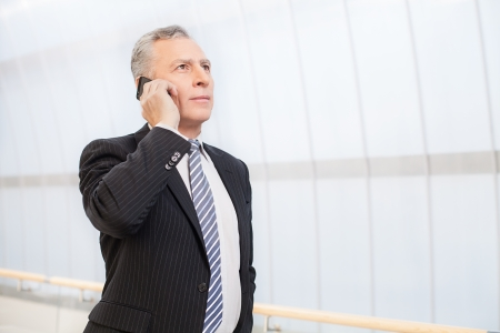 mature businessman: Confident executive. Confident senior man in formalwear talking on the mobile phone and looking away