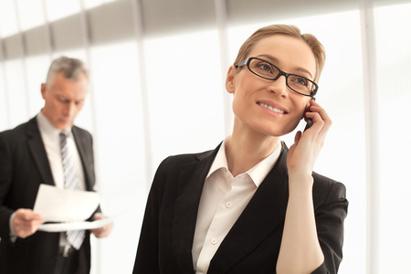 Business people at work. Beautiful mature businesswoman talking on mobile phone while man in formalwear standing on background photo