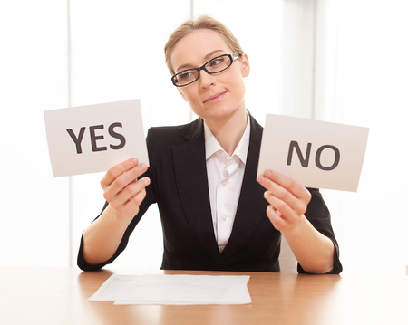 Maybe yes? Thoughtful mature woman in formalwear sitting at the table and holding papers with yes and no on them Stock Photo - 25058205