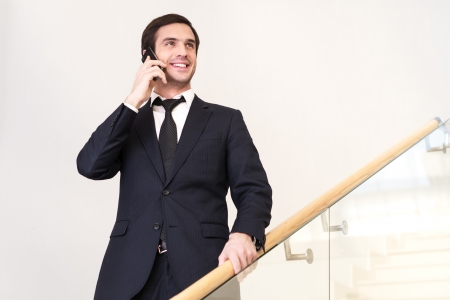 moving down: Great news! Low angle view of cheerful young man in formalwear talking on the mobile phone while moving down by staircase