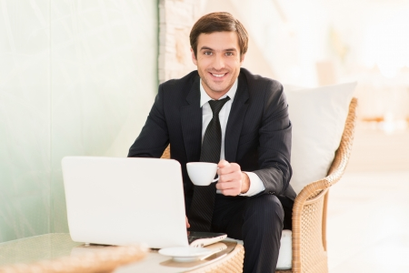 coffeebreak: I am always connected. Cheerful young businessman working at the laptop and smiling at camera while sitting at the restaurant