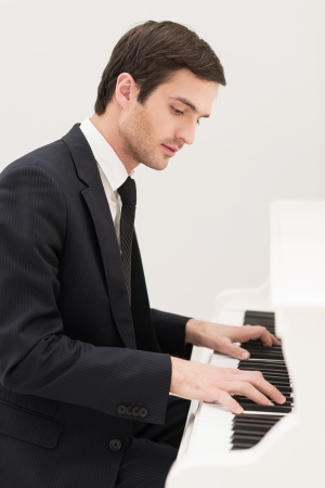 Music is everything. Confident young man in formalwear playing piano photo