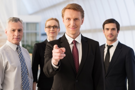 our team: Will you join our team? Confident young man in formalwear pointing you and smiling while his colleagues standing behind him