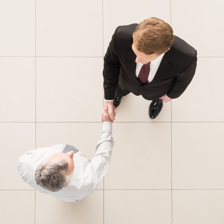 Business partners handshaking. Top view of two business men shaking hands photo