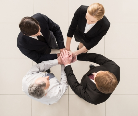 people holding hands: We are team! Top view of four people in formalwear standing close to each other and clasping their hands together