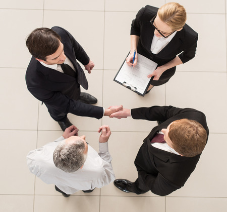 business relationship: Business meeting. Top view of four people in formalwear standing close to each other while two of them handshaking Stock Photo