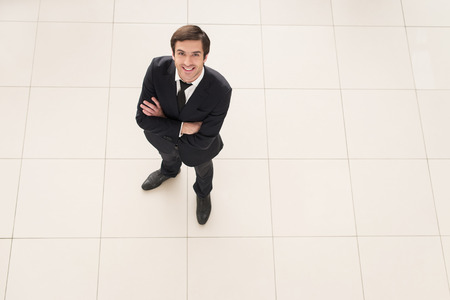 Successful businessman. Top view of cheerful young man in formalwear keeping arms crossed and smiling at camera photo
