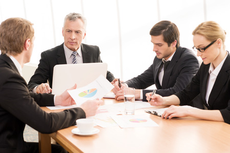 Business meeting. Four business people in formalwear discussing something while sitting together at the meeting