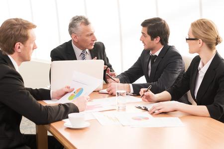 Debate caliente. Cuatro hombres de negocios en ropa formal hablando de algo mientras está sentado juntos en la reunión Foto de archivo - 25058287