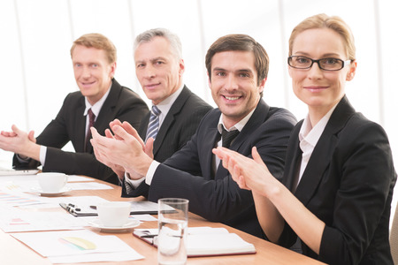 mature businessman: Applauding to you. Four people in formalwear sitting together at the table and applauding you