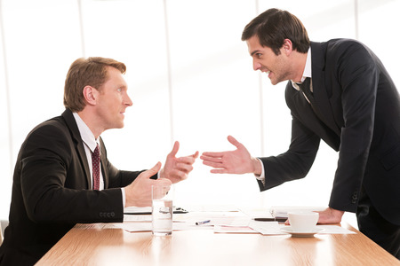 Conflits d'affaires. Deux jeunes hommes en tenues de soirée argumenter et gestes alors qu'il était assis à la table Banque d'images - 25058310