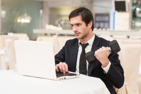 Sports and business. Confident young man in formalwear sitting at laptop and holding a dumbbell photo
