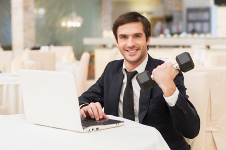 Sports and business. Smiling young man in formalwear sitting at laptop and holding a dumbbell photo