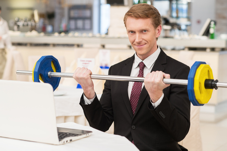 I choose healthy lifestyle. Smiling young red hair man in formalwear sitting at the restaurant and holding a dumbbell photo