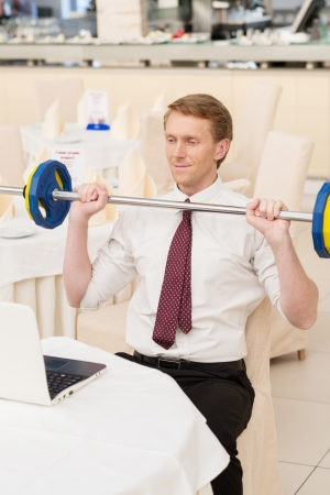 I choose healthy lifestyle. Smiling young red hair man in shirt and tie sitting at the restaurant and holding a dumbbell photo