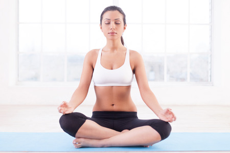 Feeling calm. Beautiful young Indian woman mediating while sitting in lotus position photo