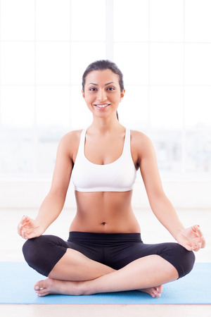 indian yoga: Fresh and calm. Beautiful young Indian woman sitting in lotus position and smiling at camera