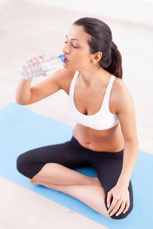 refreshed: Staying refreshed. Top view of attractive young Indian woman sitting in lotus position and drinking water
