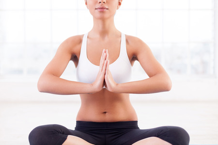 Mediation. Cropped image of attractive young Indian woman mediating while sitting in lotus position photo