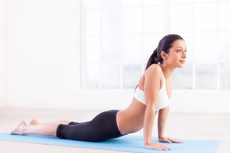 indian yoga: Woman working out. Side view of attractive young Indian woman training on yoga mat