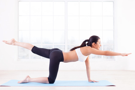 Sports training. Side view of beautiful young Indian woman training on yoga mat photo