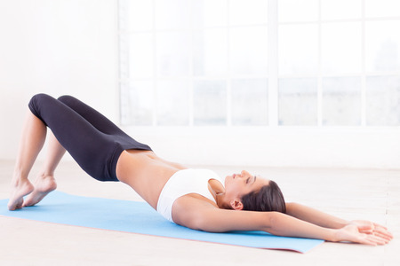 lying on side: Sports training. Side view of beautiful young Indian woman training on yoga mat