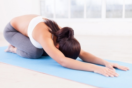 Practicing yoga. Beautiful young woman stretching on yoga mat Stock Photo