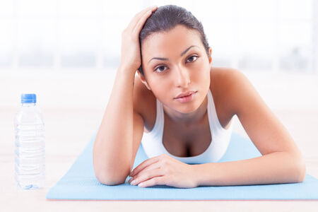 indian yoga: Tired after work out. Tired young Indian woman lying on yoga mat and looking at camera Stock Photo