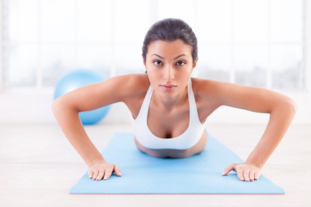 indian yoga: Woman exercising. Confident young Indian woman training on yoga mat and looking at camera